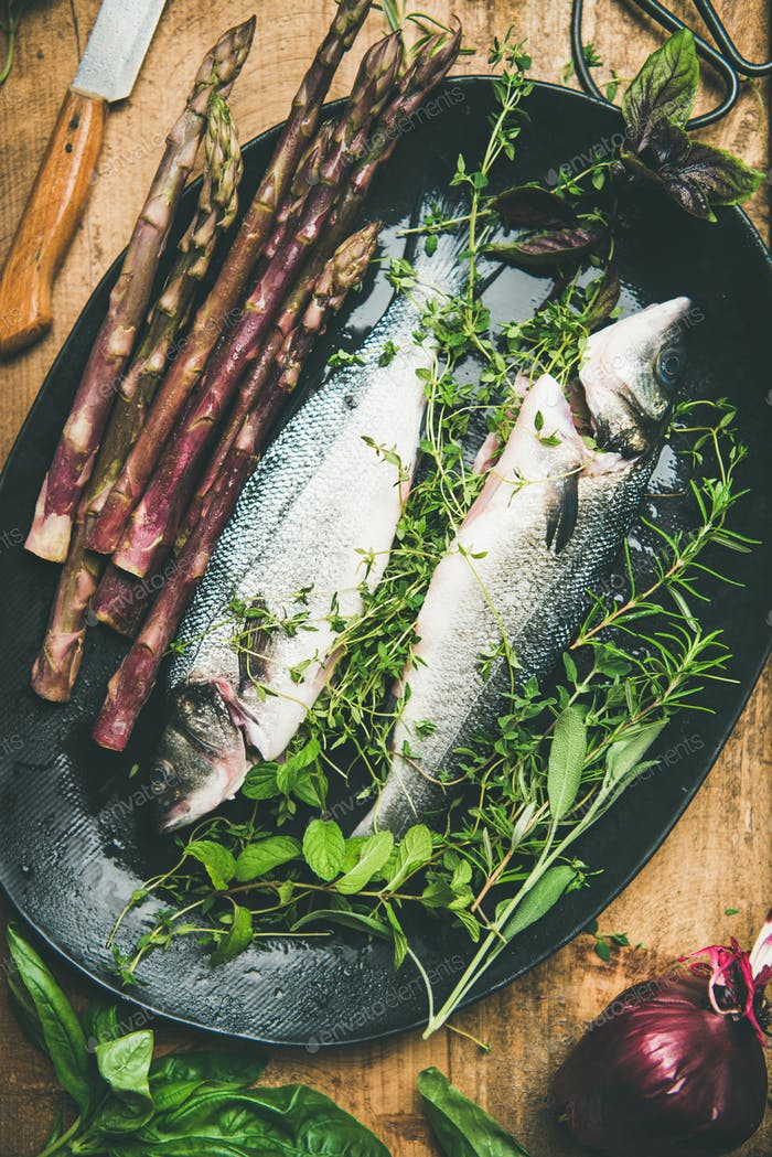 Raw uncooked sea bass fish with herbs and vegetables