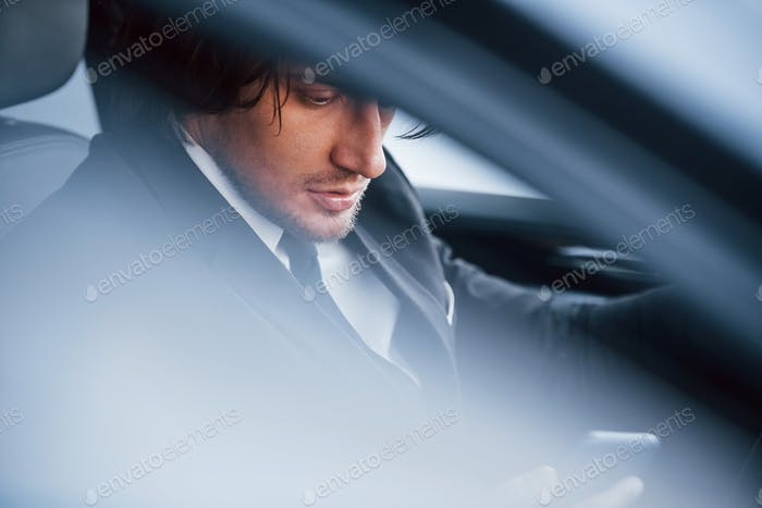 Young businessman in black suit and tie inside modern automobile