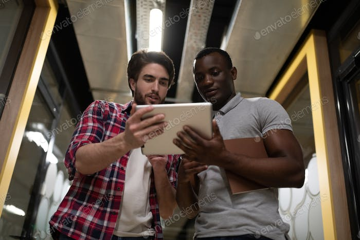 Multiethnic colleagues using tablet in office hallway