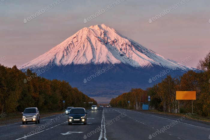 Cars Drive Along the Road On Background Volcano at Sunset Sun