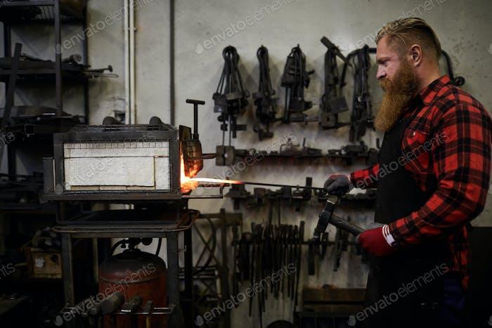 Brutal blacksmith heating steel