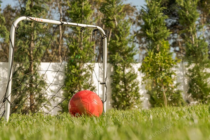 Red ball and goal in modern villa garden
