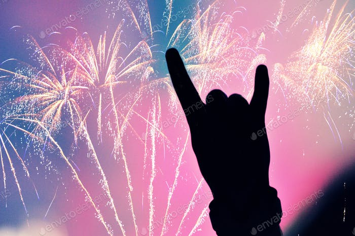 Fireworks on the sky and hand doing rock sign