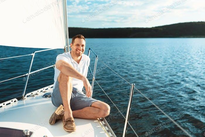 Joyful Man Sitting On Yacht Boat Deck Sailing Across Sea