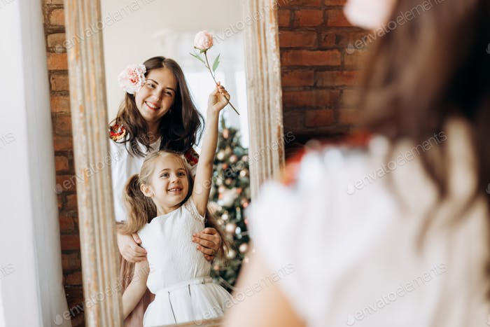 Young mother and her charming little daughter stand in front of the mirror in the room with New Year