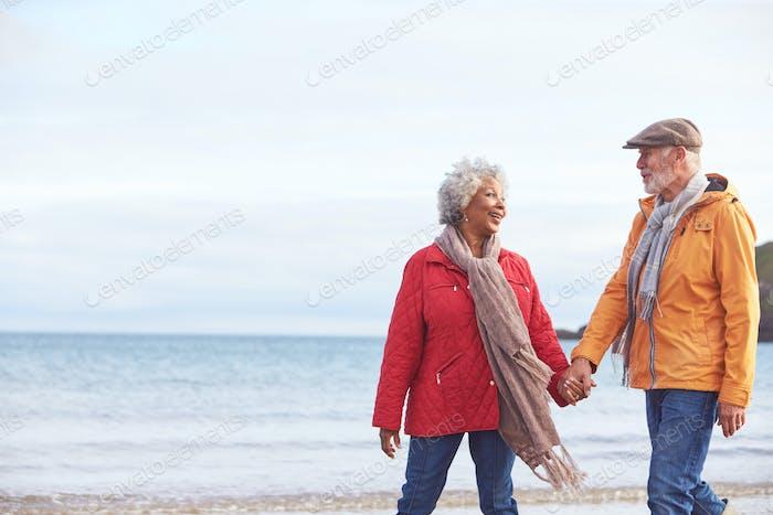 Seniorenpaar halten Hände, wie sie entlang Küste gehen auf Winter Strand Urlaub