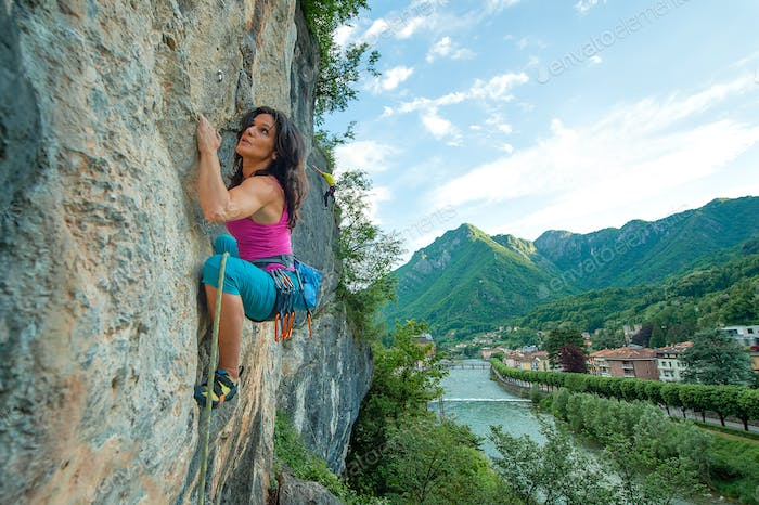 Girl practicing free climbing on rock with panorama of the villa
