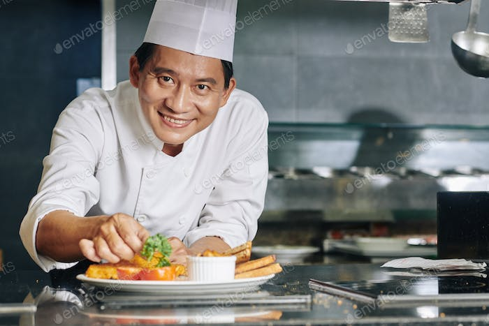 Asian chef with dish at the restaurant