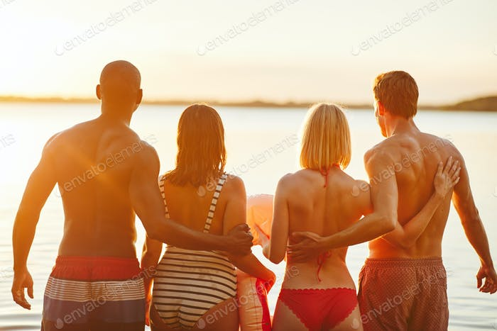 Two couples in swimwear watching the sunset over a lake