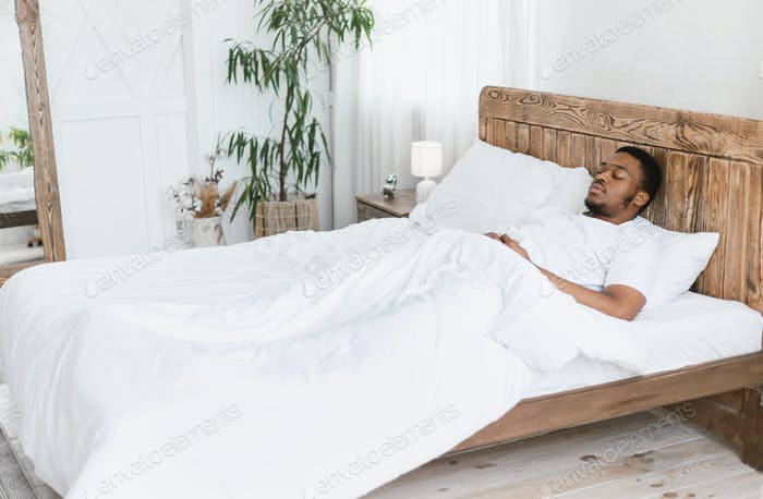 African Man Sleeping Lying With Eyes Closed In Bed Indoors