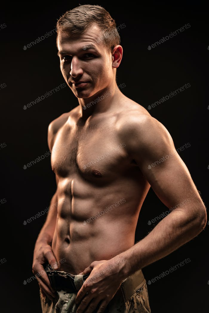 Studio shot of muscular topless military man on black background