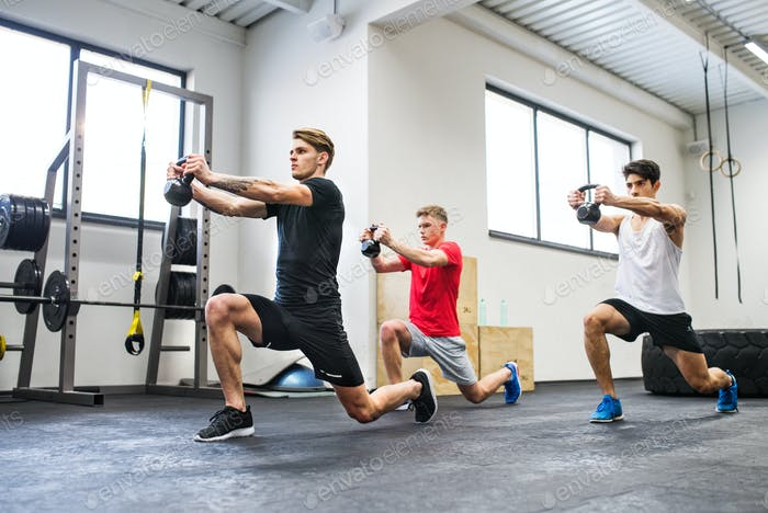 Three young men in gym doing exercise with kettlebells.