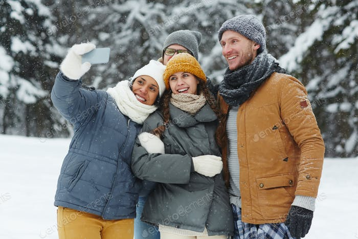 Excited friends taking selfie in winter forest