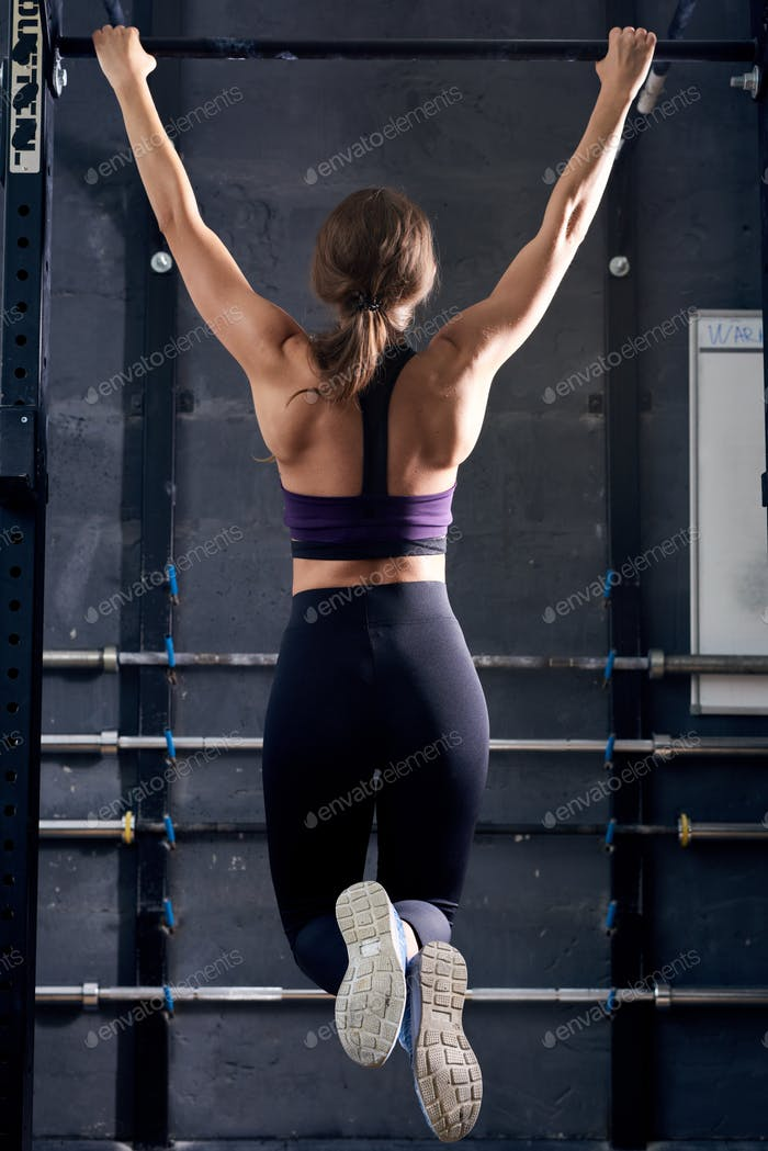 Muscular Woman Doing Pull Ups in Crossfit Gym