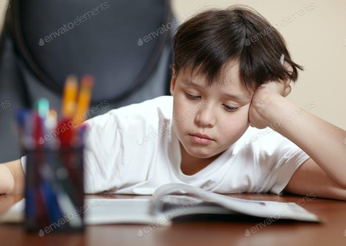 Schuljunge studiert hart über sein Buch zu Hause