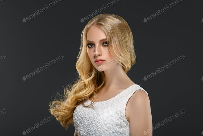 Curly long hair blonde young model. Beauty girl with curly perfect hairstyle