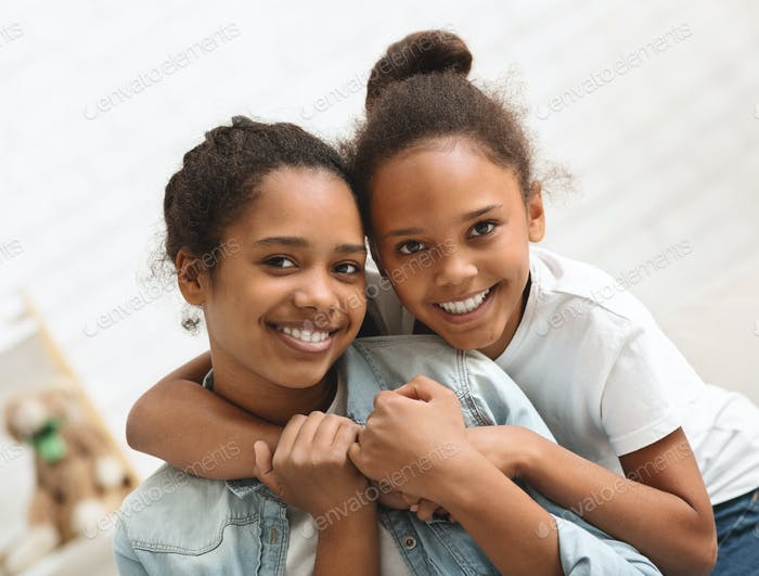 Portrait of two lovely african sisters bonding at home