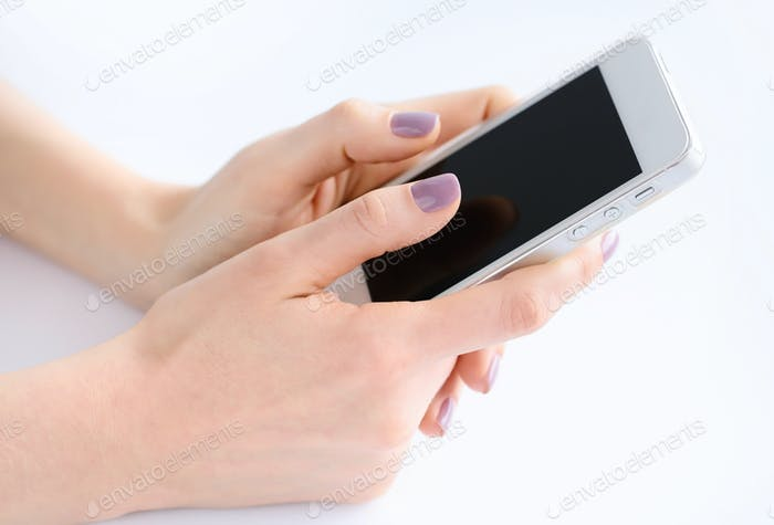 Women's hands holding mobile phone, fingers touching the screen