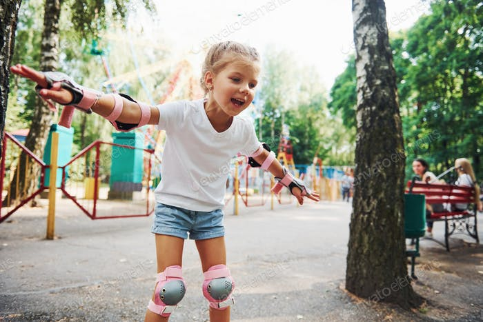 Photo in motion. Cheerful little girl on roller skates have a good time in the park near attractions