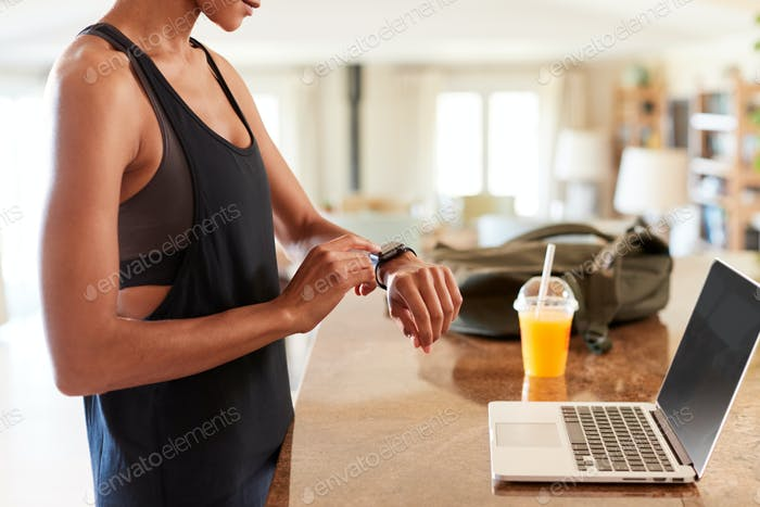 Mid section of African American woman checking fitness app on smartwatch after the gym