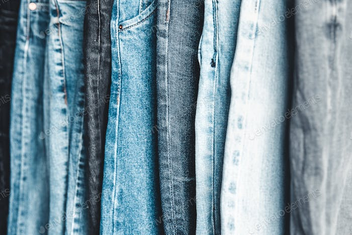 Rack with different jeans on grey background