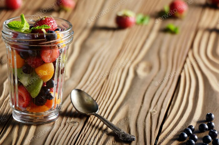 Assorted berries in mason jar on kitchen wooden table with spoon