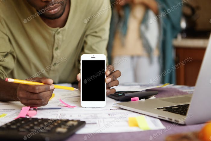 Technology and advertising concept. Cropped shot of African-American man holding mobile phone and po