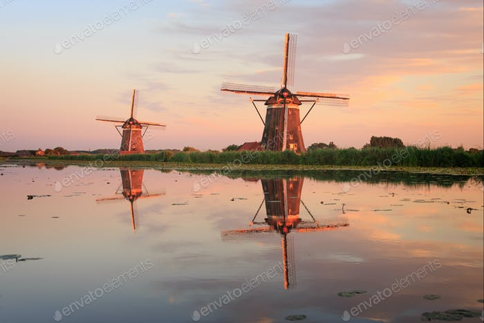Two windmills with reflection at sunset