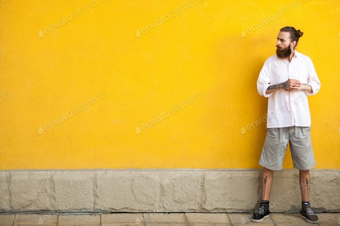 Tattooed bearded hipster on yellow wall
