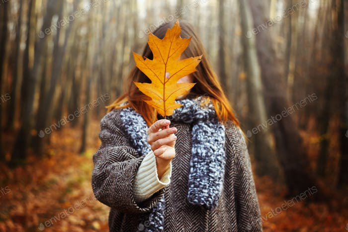 beautiful stylish happy gorgeous girl holding yellow leaf