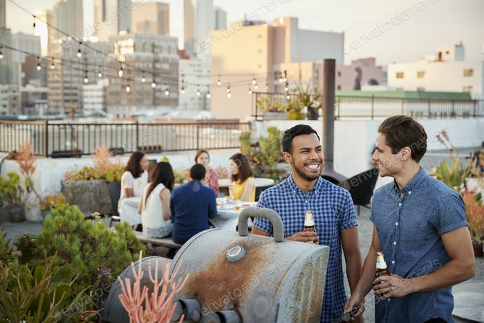Friends Gathered On Rooftop Terrace For Barbecue With City Skyline In Background
