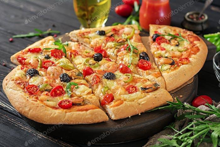 Köstliche Meeresfrüchte Garnelen und Muscheln Pizza auf einem schwarzen Holztisch. Italienisches Essen.