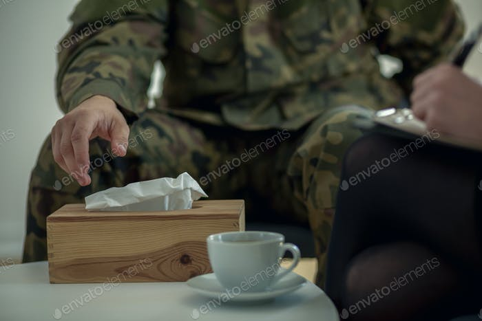 Close-up of a soldier's hand taking a tissue from a box during t