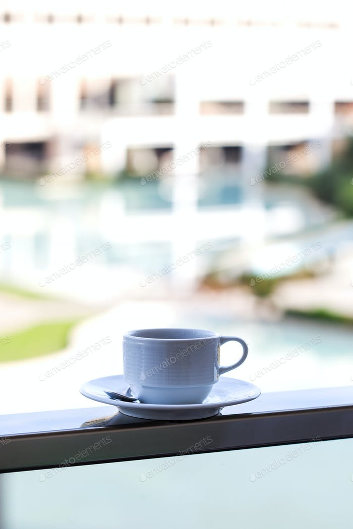 White mug on a white saucer with coffee on the outdoor pool on site.