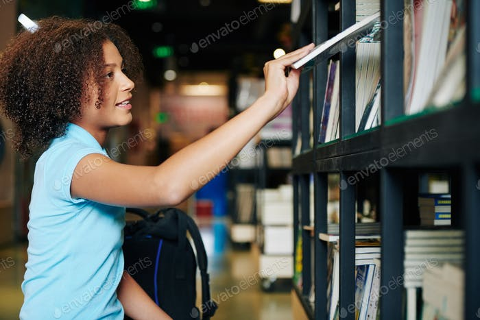 Mädchen nehmen Buch in Buchhandlung