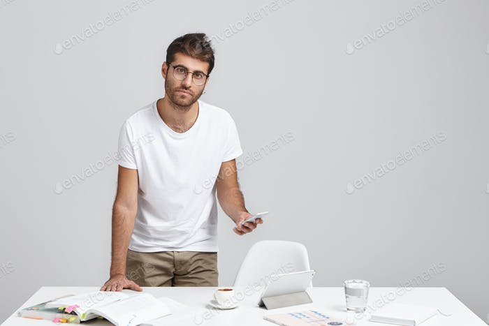 Schöner junger männlicher Wirtschaftslehrer mit Stoppeln am weißen Schreibtisch mit Lehrbüchern, Grafiken,