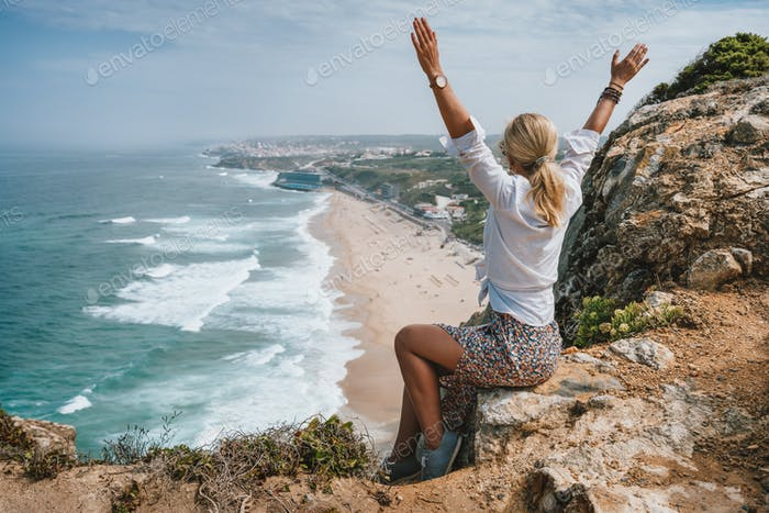 Beautiful women raising hands enjoying atlantic ocean coast on Praia da Adraga, Sintra, Portugal