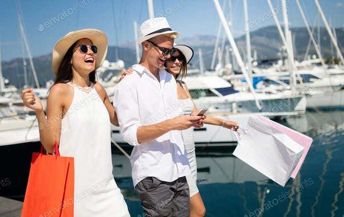 Consumerism, friends, vacation, travel concept. Beautiful people enjoying shopping having fun