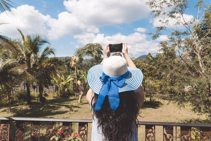 Young Woman In Hat Make Photograph Of Tropical Forest Landscape From Balcony Or Terrace