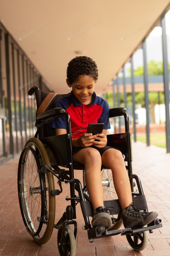 happy disabled schoolboy using mobile phone in corridor at elementary school