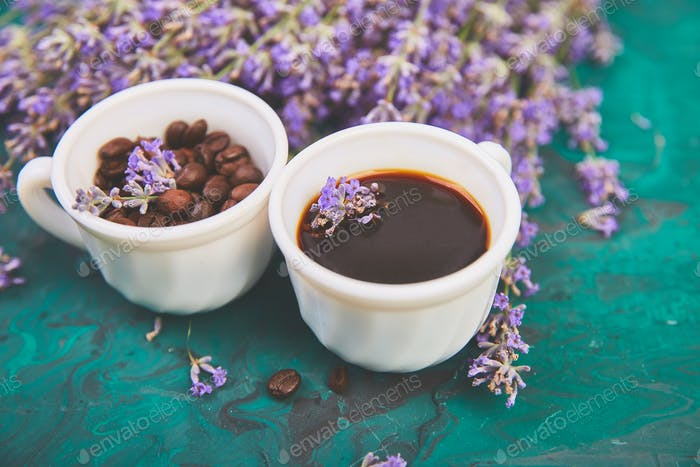 Coffee, coffee grain in cups and lavender flower on green background