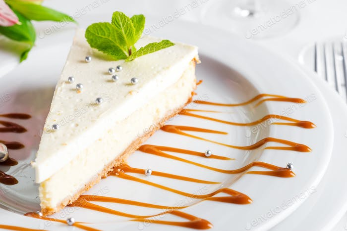 Classical New York Cheesecake with mint on white plate close up
