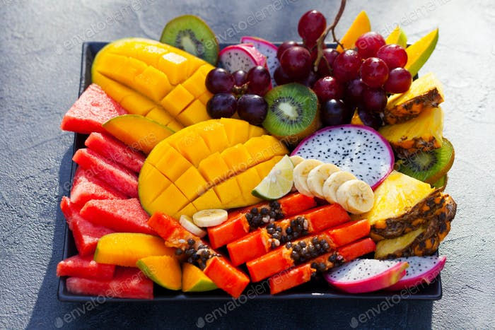 Tropical Fruits Assortment on a Plate. Grey Background. Close up.