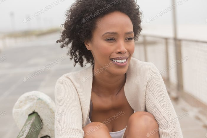Front view of happy young African American woman sitting on bench at promenade. She is smiling