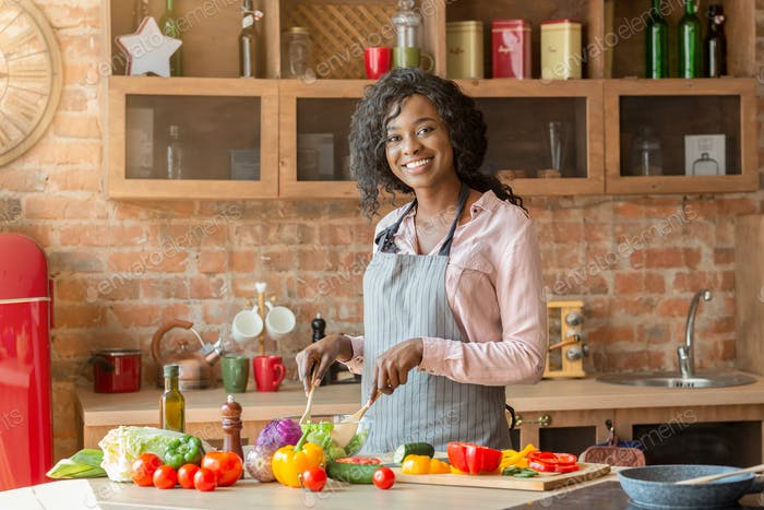 fröhlich afrikanische Dame mischen Gemüse in Schüssel in Küche