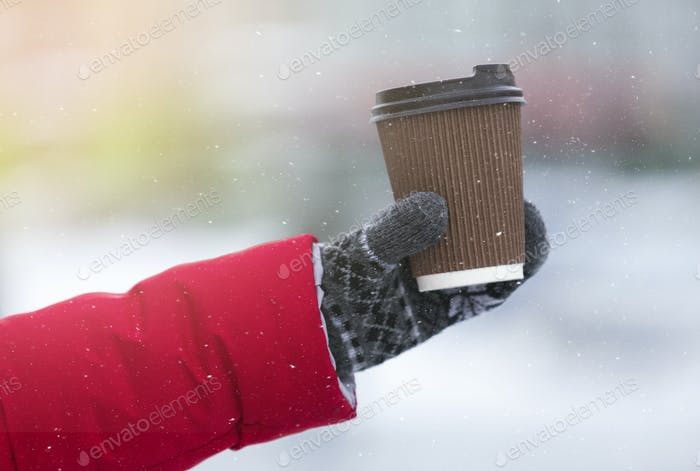 Female hand in glove holding cup with hot tea, coffee