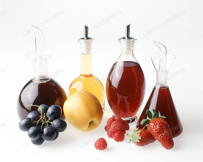 An assortment of fruit vinegars with fresh fruit