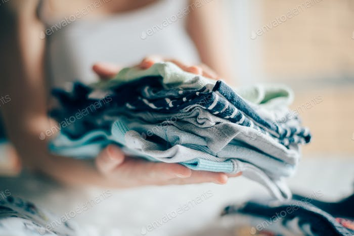 Thumbnail for Mother sorting newborn baby clothing at home