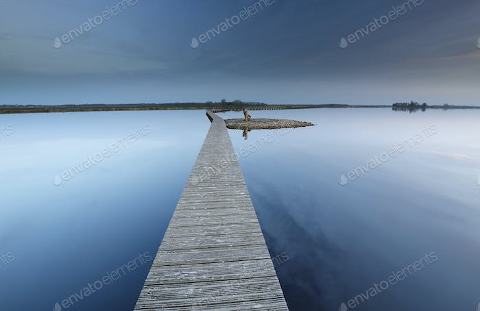wooden walkway on water to island with bench