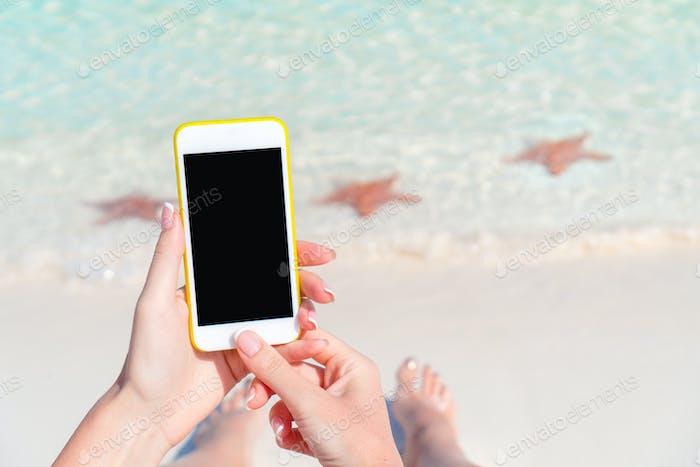 Primer teléfono inteligente en manos femeninas en el fondo del océano turquesa en la playa tropical